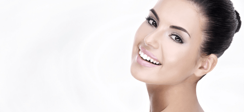 Collagen banner - feature image of beautiful smiling woman with brown hair in a bun looking at the camera.