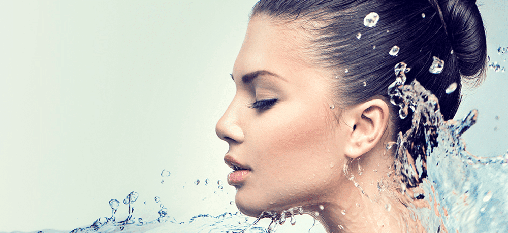 feature image for hydrafacial treatment of brunette with her hair in a bun and water splashing around her face