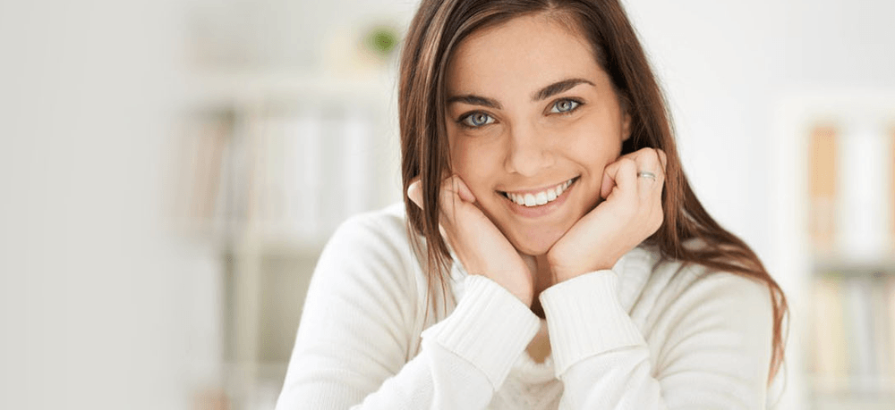 Votiva Vaginal Rejuvenation - Smiling woman as background image for votiva treatment
